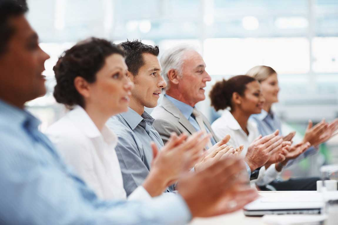 Multi ethnic coworkers sitting in a line and applauding at conference table